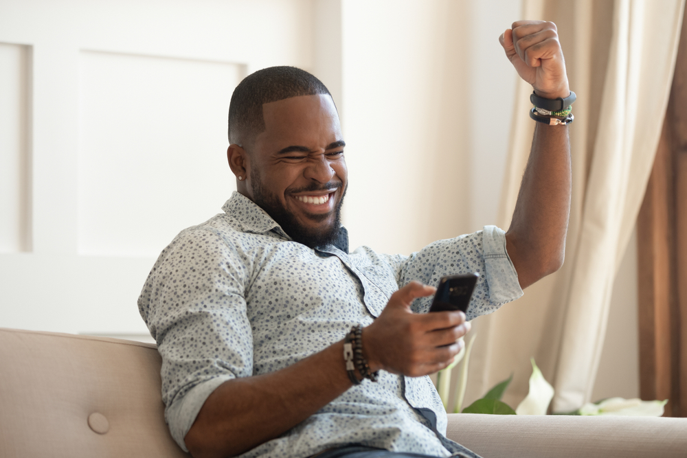 Approved Mortgage - a man excited about something on his phone